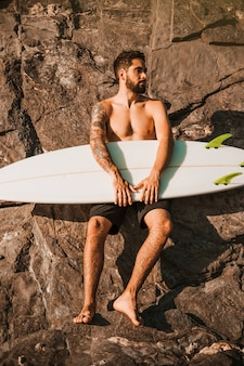 Young bearded man holding surf board near stones