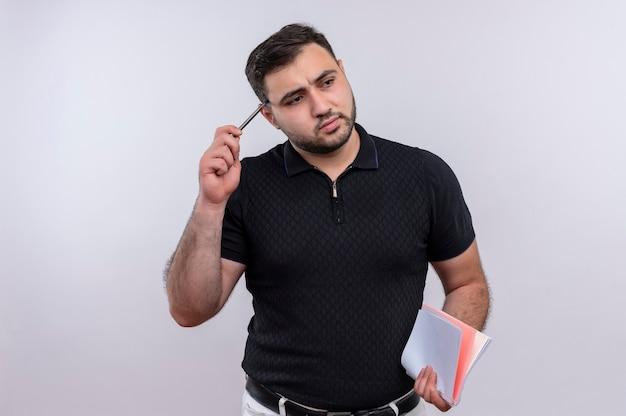 顔に物思いにふける表情で脇を見てペンでノートを保持している黒いシャツの若いひげを生やした男