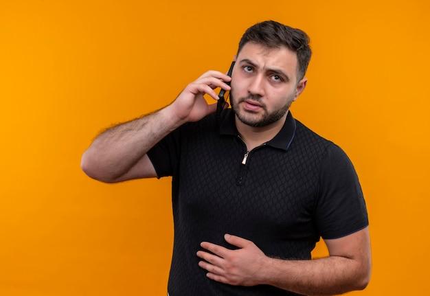 Молодой бородатый мужчина в черной рубашке выглядит смущенным и очень обеспокоенным во время разговора по мобильному телефону