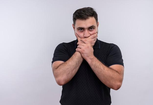 黒のシャツを着た若いひげを生やした男が手で口を覆ってショックを受けた
