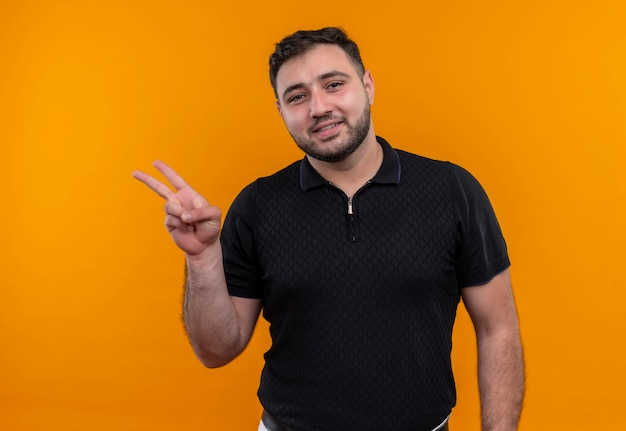 Молодой бородатый мужчина в черной рубашке, весело улыбаясь, показывая знак победы
