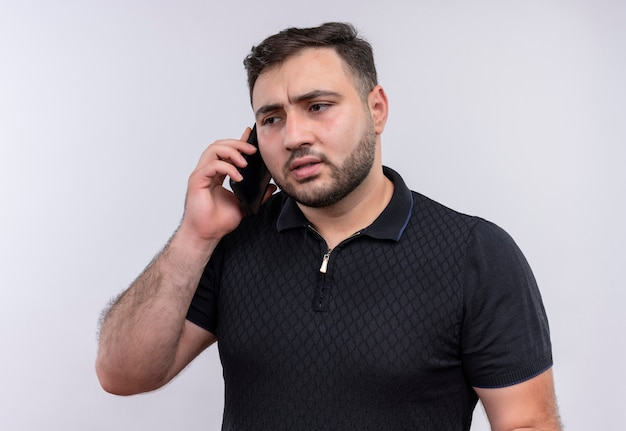 Молодой бородатый мужчина в черной рубашке разговаривает по мобильному телефону с серьезным лицом