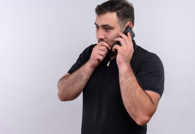 Молодой бородатый мужчина в черной рубашке рассказывает секрет во время разговора по мобильному телефону