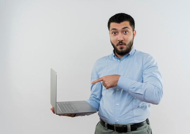 白い壁の上に立って驚いて人差し指で指しているラップトップを保持している青いシャツの若いひげを生やした男