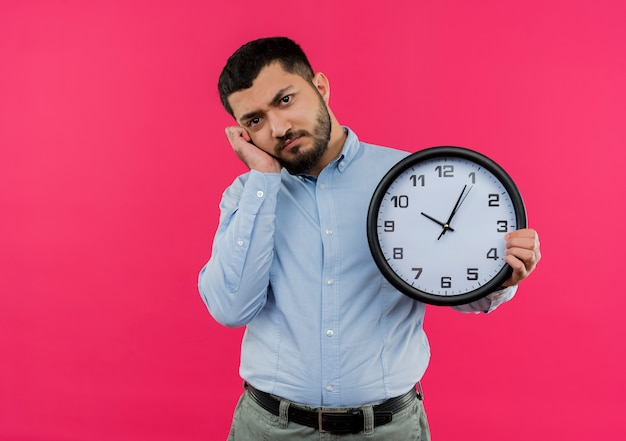 疲れて退屈している壁時計を保持している青いシャツの若いひげを生やした男