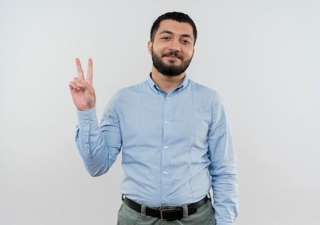 Молодой бородатый мужчина в синей рубашке улыбается, показывая v-знак