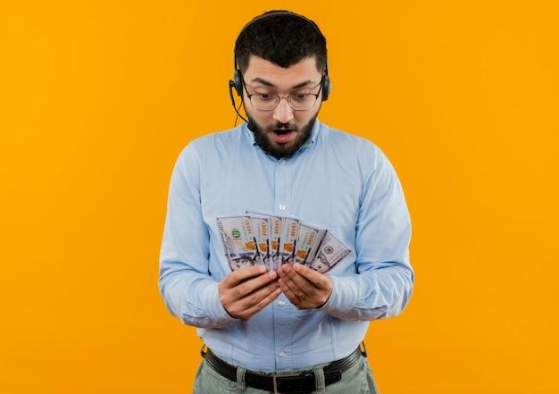 Молодой бородатый мужчина в синей рубашке с наушниками с микрофоном, держащий деньги, выглядит удивленным и удивленным, стоя над оранжевой стеной