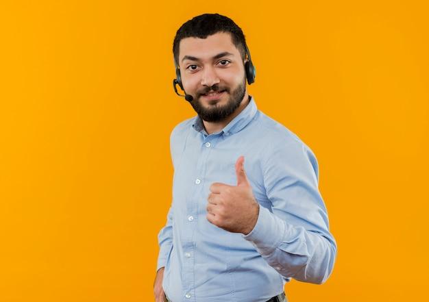 Молодой бородатый мужчина в синей рубашке с наушниками с микрофоном, глядя на фронт, улыбаясь, показывает палец вверх, стоя над оранжевой стеной