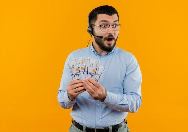 Молодой бородатый мужчина в синей рубашке с наушниками с микрофоном показывает деньги счастливыми и удивленными