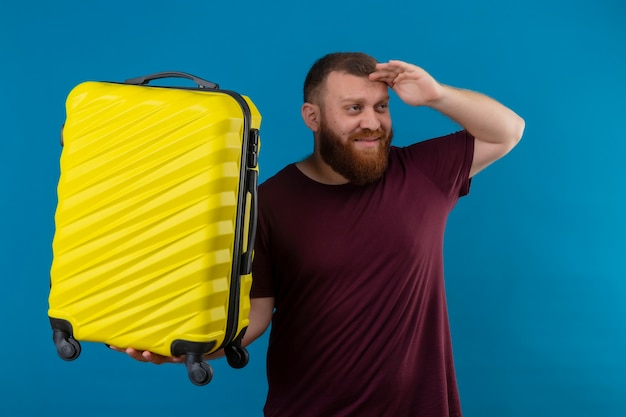 茶色のtシャツを着た若いひげを生やした男が何かを見るために頭上に手を渡して遠くを見ている旅行スーツケースを保持しています