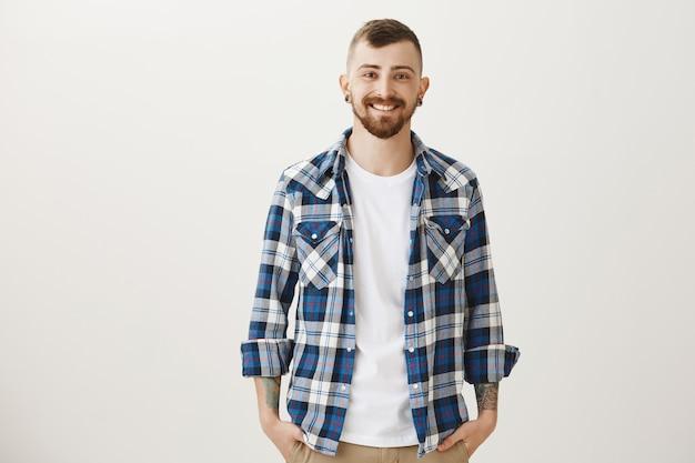 Молодой бородатый мужчина в повседневной рубашке улыбается
