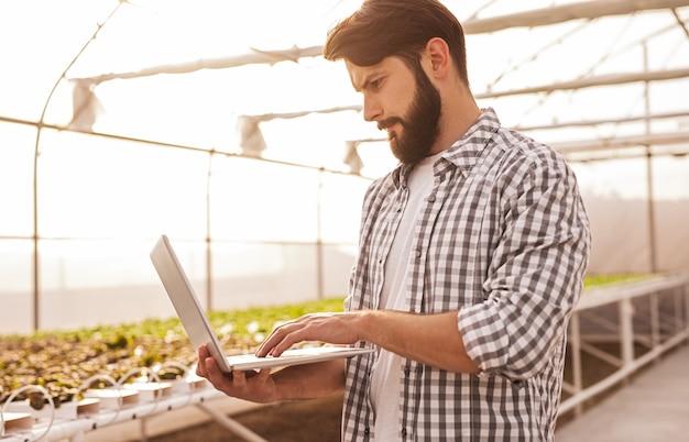 Молодой бородатый мужчина в клетчатой рубашке использует ноутбук для управления автоматическим поливом в современной гидропонной теплице
