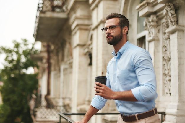 안경을 쓰고 정장을 입은 젊은 수염 난 남자가 커피 한 잔을 들고 멀리 바라보고 있다