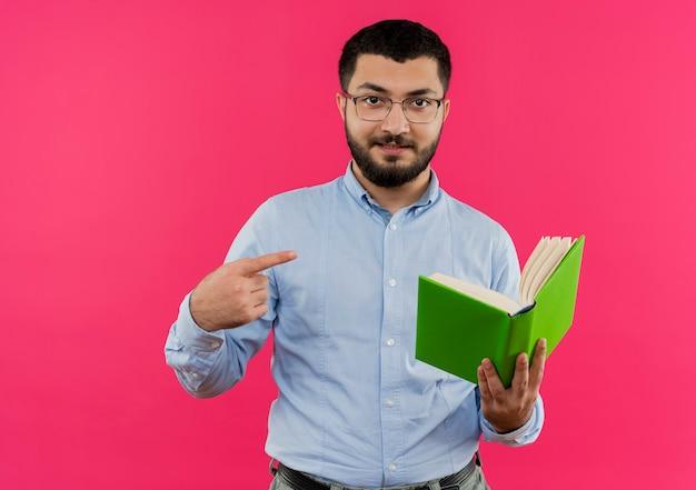 眼鏡と青いシャツを着た若いひげを生やした男が自信を持って笑ってそれを指で指している本を保持