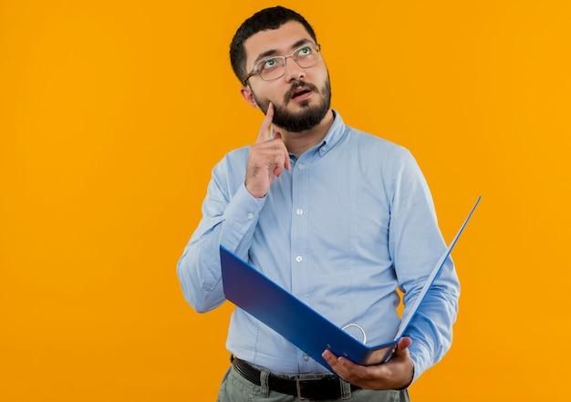 Молодой бородатый мужчина в очках и синей рубашке держит папку, глядя вверх с задумчивым выражением лица