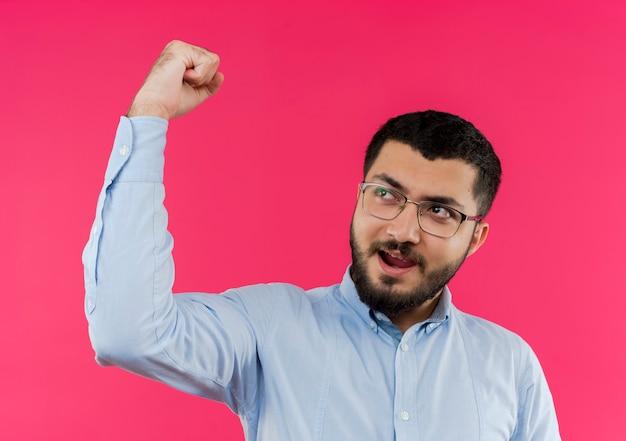 Молодой бородатый мужчина в очках и синей рубашке смотрит в сторону, сжимая кулак, возбужденный