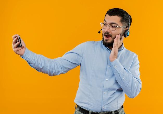 Молодой бородатый мужчина в очках и синей рубашке с наушниками с микрофоном делает селфи, используя свой смартфон, улыбаясь, будучи удивленным