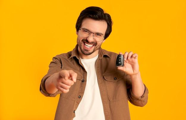 Молодой бородатый мужчина в очках держит ключи дистанционного управления от нового изолированного автомобиля. покупка, аренда авто.