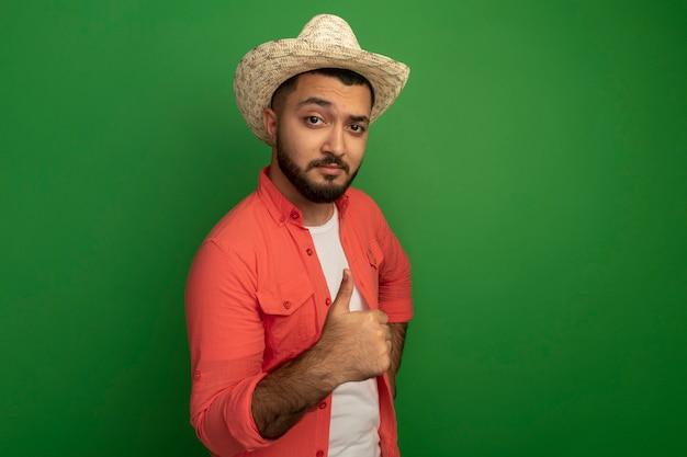 오렌지 셔츠와 여름 모자에 젊은 수염 난된 남자가 녹색 벽 위에 서서 sjowing 엄지 손가락을 찾고