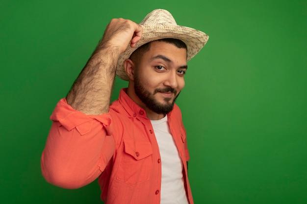 오렌지 셔츠와 여름 모자에 젊은 수염 남자 녹색 벽 위에 자신감 서 웃 고 찾고