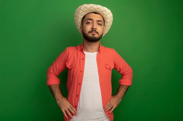 오렌지 셔츠와 여름 모자에 젊은 수염 난된 남자 녹색 벽 위에 서 심각한 자신감 expresion으로 찾고