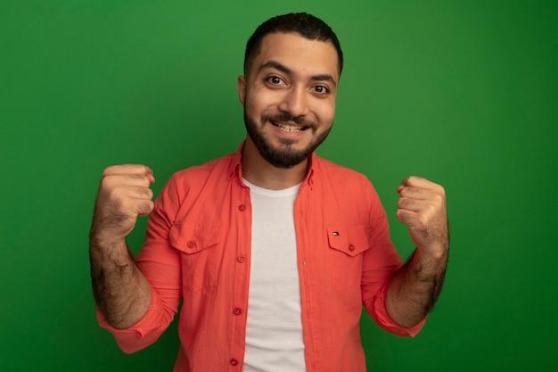 오렌지 셔츠에 젊은 수염 난 남자 주먹을 떨림 행복하고 흥분 녹색 벽 위에 서 그의 성공을 기뻐