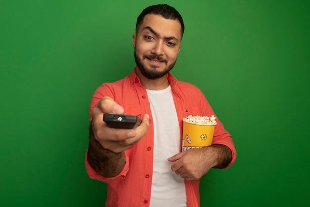 Молодой бородатый мужчина в оранжевой рубашке держит ведро с попкорном, используя пульт от телевизора, смущенно глядя на него, стоя у зеленой стены