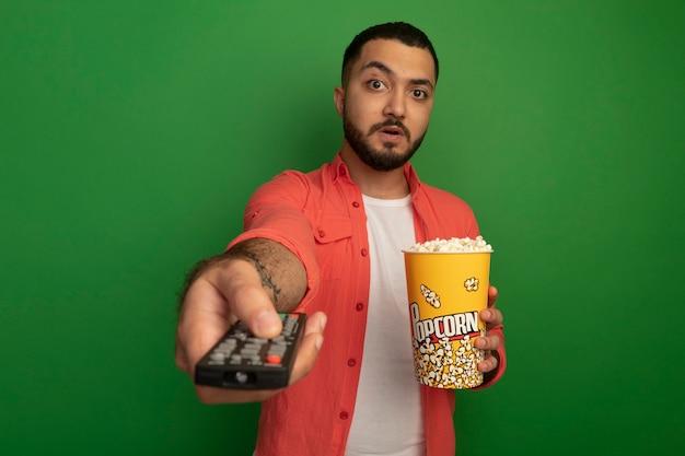Молодой бородатый мужчина в оранжевой рубашке держит ведро с попкорном, используя пульт от телевизора, выглядит удивленным, стоя у зеленой стены