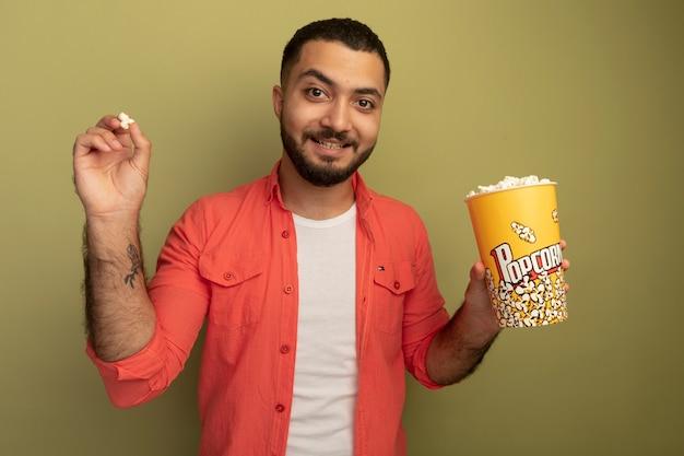 明るい壁の上に元気に立って笑っているポップコーンとバケツを保持しているオレンジ色のシャツの若いひげを生やした男
