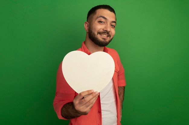 緑の壁の上に立っている顔に笑顔で見て段ボールの心を保持しているオレンジ色のシャツの若いひげを生やした男