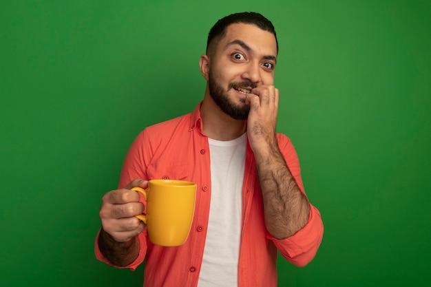 緑の壁の上に立っているマグカップストレスと神経質な噛む爪を保持しているオレンジ色のシャツの若いひげを生やした男