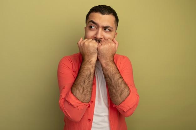 明るい壁の上に立っているストレスと神経質な噛む爪を脇に見ているオレンジ色のシャツの若いひげを生やした男