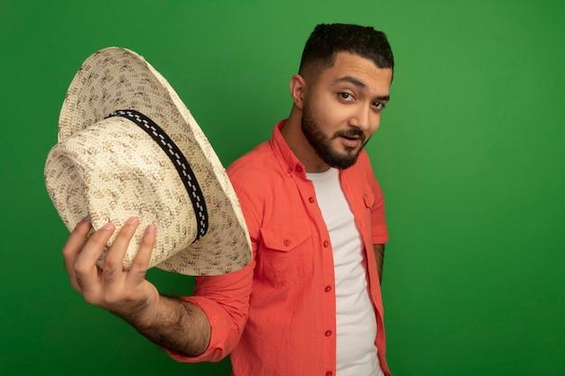 녹색 벽 위에 자신감 서 웃 고 그의 여름 모자를 보여주는 오렌지 셔츠에 젊은 수염 난된 남자