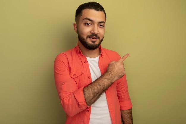 明るい壁の上に立っている人差し指で後ろを指して微笑んでいるオレンジ色のシャツの若いひげを生やした男