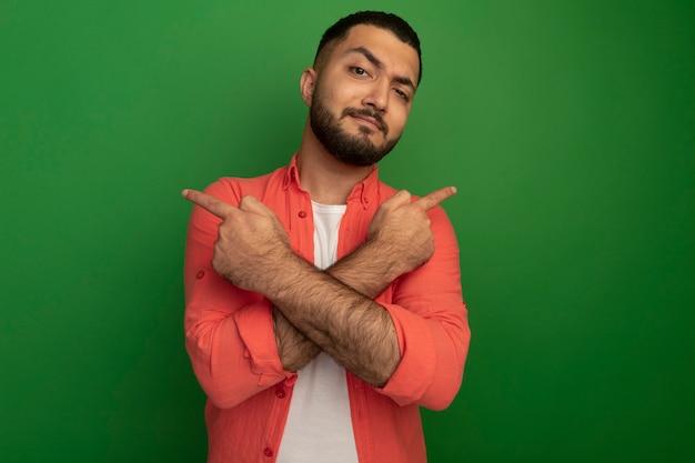 緑の壁の上に立っている反対側にインデックスfignersで指している自信を持って表情を持つオレンジ色のシャツの若いひげを生やした男