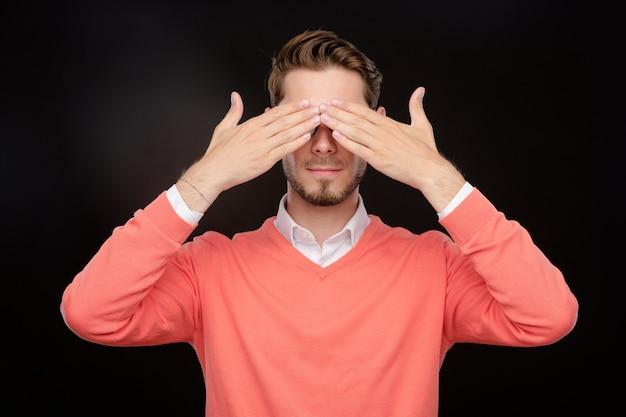 숨바꼭질을하거나 무서워하는 동안 손으로 눈을 감고있는 주황색 스웨터에 수염 난 젊은이
