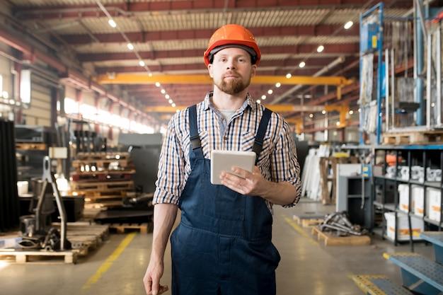 Молодой бородатый мужчина в комбинезоне и шлеме позирует в одном из крупных заводских цехов