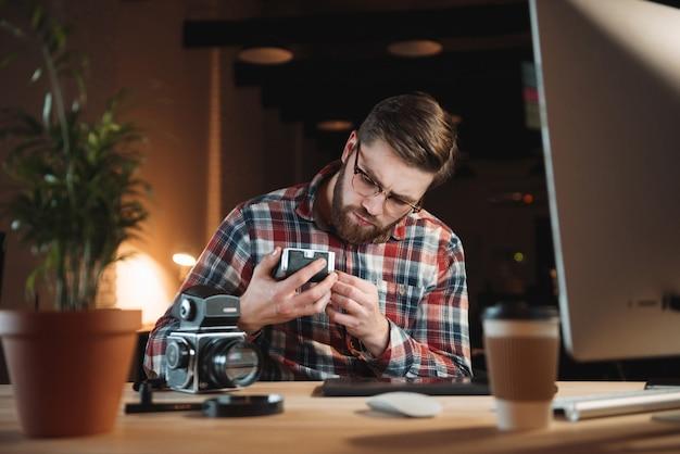 Молодой бородатый мужчина в клетчатой рубашке пытается починить старую камеру, сидя на своем рабочем месте