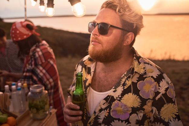 해변에서 파티에서 친구들과 함께 맥주를 마시는 선글라스를 쓴 수염난 청년