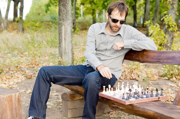 Молодой бородатый мужчина в солнечных очках сидит на деревянной скамейке в парке и планирует свой следующий шахматный ход