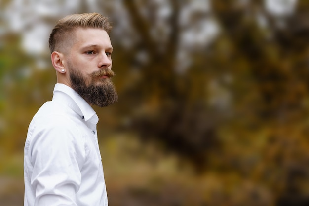 白いシャツを着た若いひげを生やした男は、自然の中で一人で時間を過ごして公園で黄色い秋の日に歩きます...