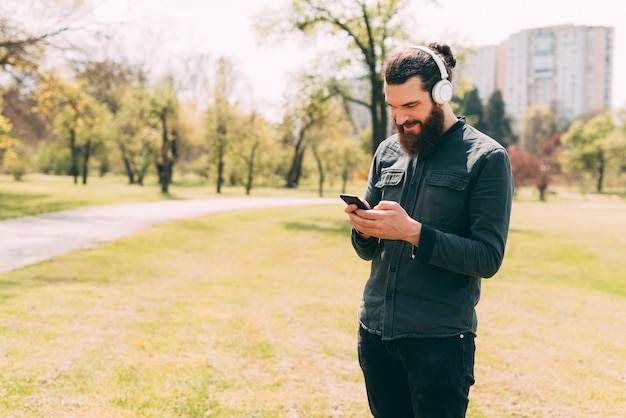 A young bearded man is happily chatting with someone with his headphones on in park