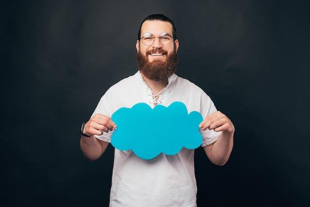 Молодой бородатый мужчина держит синее бумажное облако.