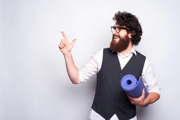 Молодой бородатый мужчина держит коврик для йоги