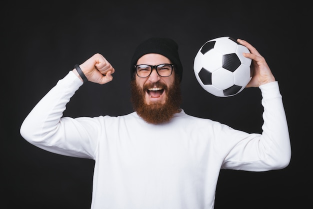 Young and bearded man is holding a soccer ball and celebrating near black wall.