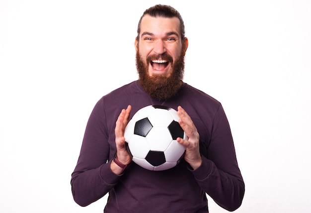 Young bearded man is looking excited at the camera and holding a soccer ball