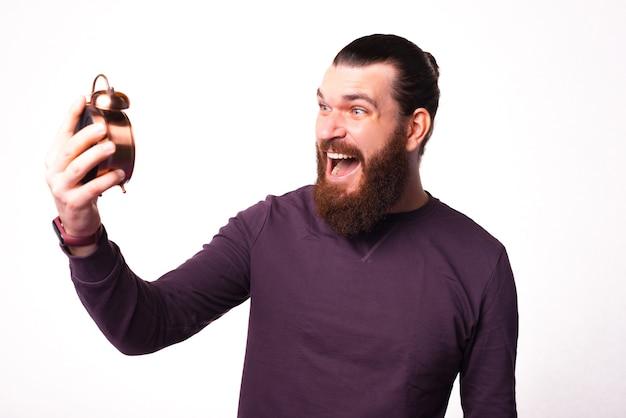 若いひげを生やした男は彼が白い壁の近くで保持している時計でストレスを感じている