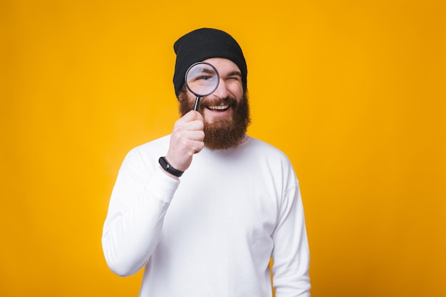 Young bearded man is looking through a magnifying glass and smiling near yellow wall.