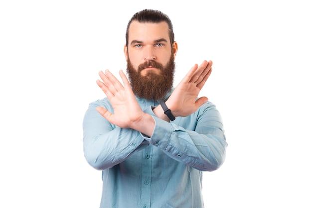 Молодой бородатый мужчина делает запрещенный знак на белом фоне.