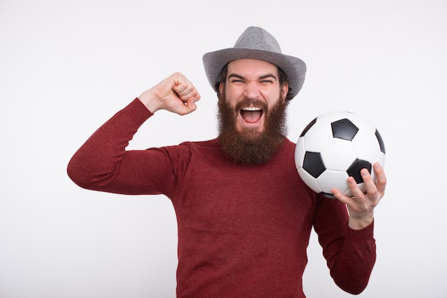 Young bearded man is screaming and holding a soccer ball.